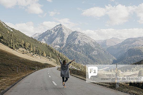 Schweiz  Engadin  Rückansicht einer glücklichen Frau mit erhobenen Armen auf einer Bergstrasse