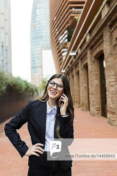 Glückliche junge Geschäftsfrau am Handy in der Stadt