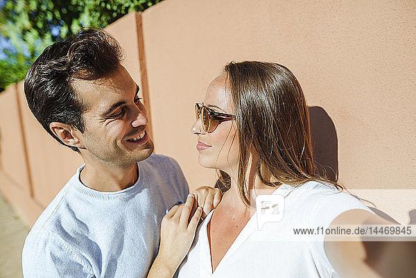 Selfie eines lächelnden Paares  das sich an einem sonnigen Tag anschaut