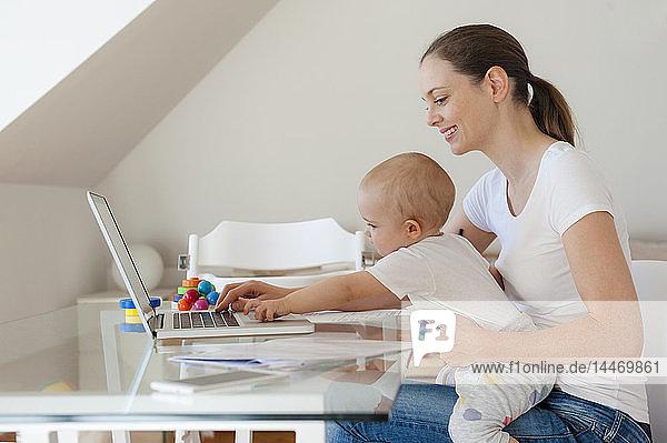 Lächelnde Mutter und kleine Tochter mit Laptop gemeinsam am Tisch zu Hause