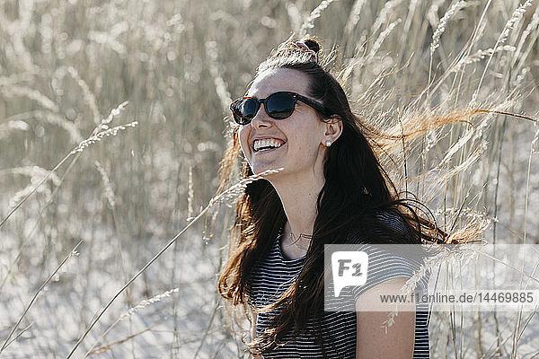 Südafrika  Western Cape  Hout Bay  Porträt einer lachenden jungen Frau in den Dünen