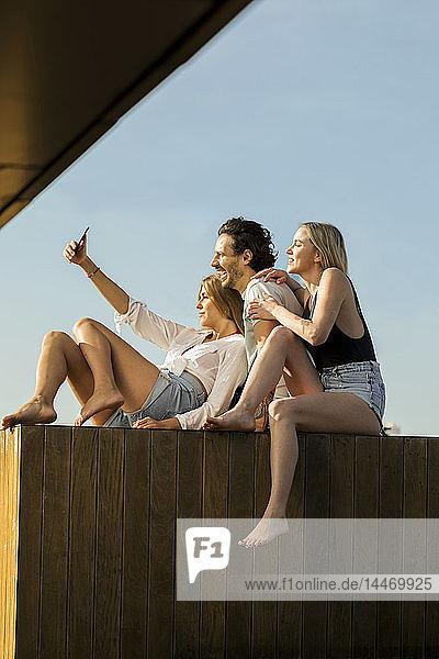 Freunde amüsieren sich auf einer Dachterrasse und nehmen sich selbst