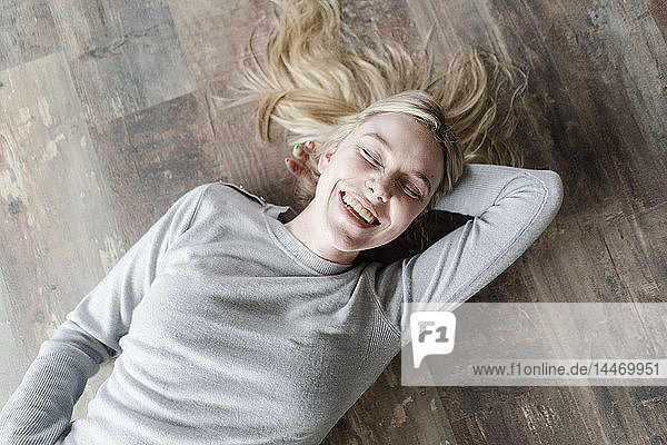 Happy blond young woman lying on wooden floor