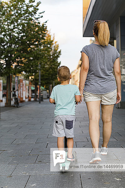 Mutter und ihr Sohn auf einem Roller in der Stadt