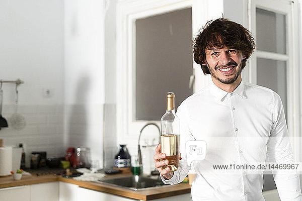 Mann steht in der Küche und hält eine Flasche Weißwein