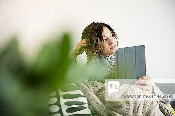 Woman sitting on couch  wrapped in a blanket  reading e-book