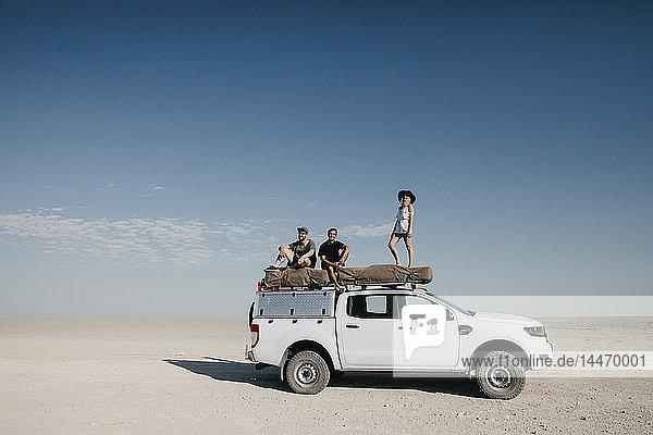 Freunde auf einer Safari  auf ihrem Geländewagen stehend