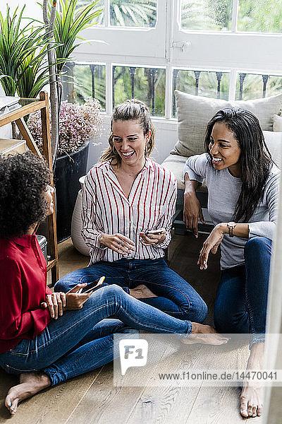 Drei glückliche Frauen sitzen zu Hause mit Mobiltelefonen auf dem Boden