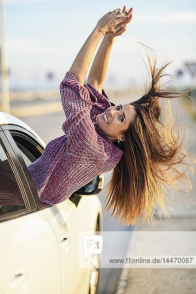 Porträt einer glücklichen Frau  die sich aus dem Autofenster lehnt