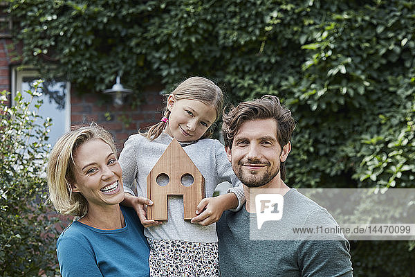 Portrait of happy family in front of their home with house model