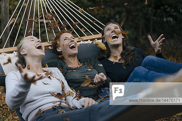 Sorglose Mutter mit zwei Teenager-Mädchen  die im Garten Herbstblätter in die Hängematte werfen