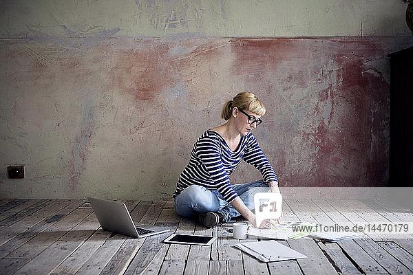 Frau sitzt auf Holzboden in einem unrenovierten Zimmer eines Dachgeschosses und arbeitet