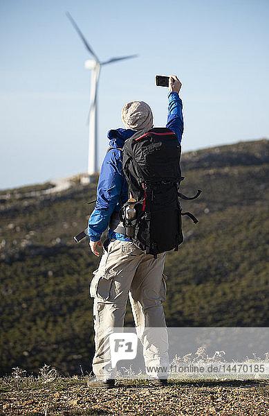 Spanien  Andalusien  Tarifa  Mann auf Wanderung mit einem Selfie mit Windrad im Hintergrund