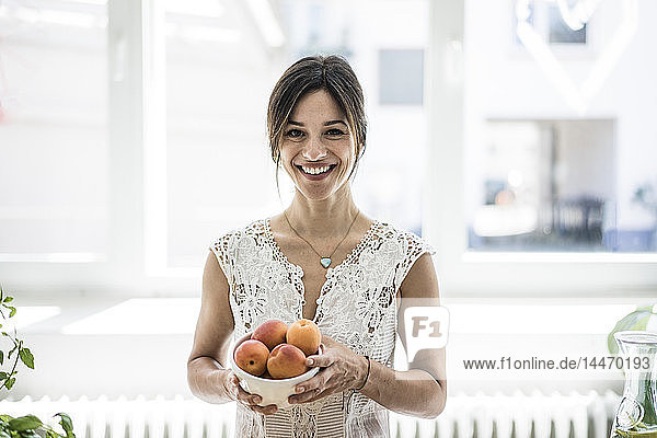Woman holding bol of apricots in her kitchen
