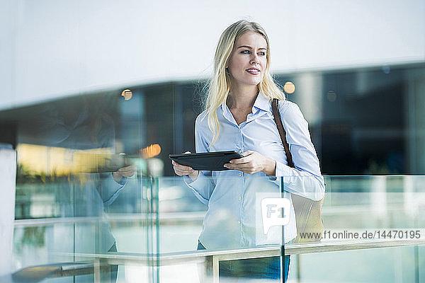 Blonde Frau mit Tablette steht am Glasgeländer in der Stadt