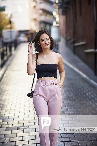 Porträt einer lächelnden jungen Frau mit Kamera  die auf der Straße geht