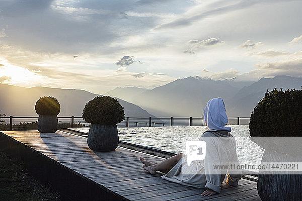 Frau  die sich am Pool entspannt  Bademantel und Turban trägt