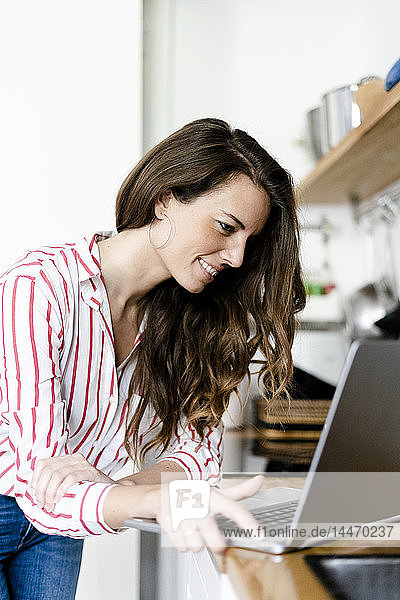 Smiling woman using laptop in kitchen at home