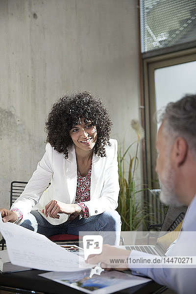 Smiling businesswoman handing over document to colleague in a loft