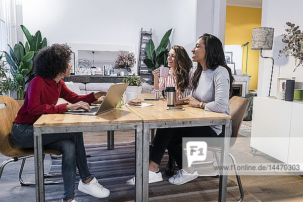 Three happy women with laptop at table