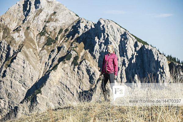 Österreich  Tirol  lächelnde Athletin auf Almwiese stehend