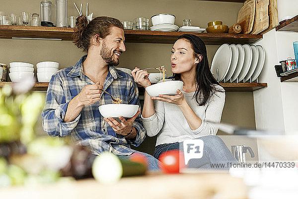 Glückliches Paar sitzt in der Küche und isst Spaghetti