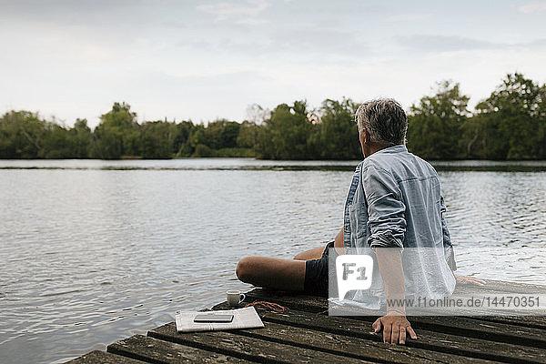 Älterer Mann sitzt auf einem Steg an einem See