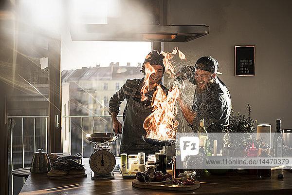 Freunde flambieren Lebensmittel in einer Pfanne und erzeugen eine große Flamme