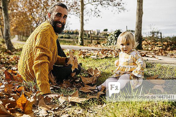 Vater und Tochter sitzen auf einer Wiese mit Herbstlaub  morgens im Park