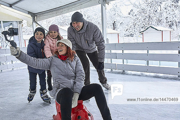 Family with two kids on the ice rink  taking selfies with their smartphone