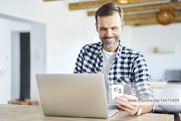 Cheerful man using phone while working on laptop at home
