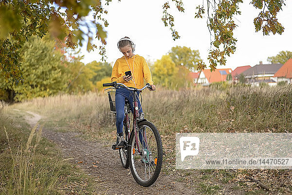 Girl with headphones sitting on bicycle looking at smartphone