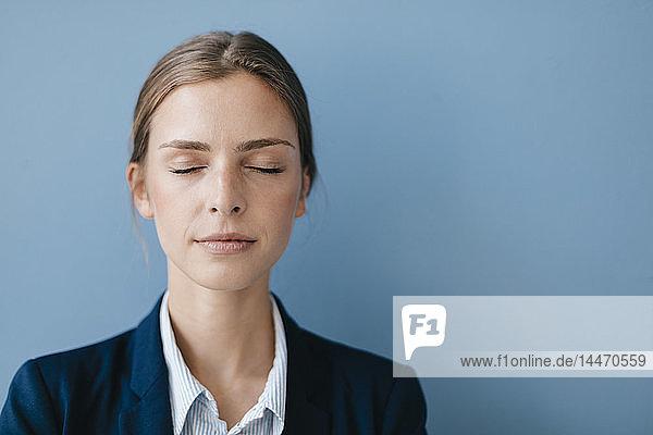 Porträt einer jungen Geschäftsfrau vor blauem Hintergrund  die sich mit geschlossenen Augen entspannt