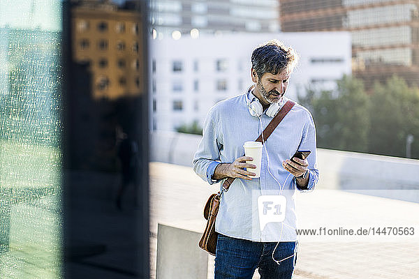 Mature man with takeaway coffee and headphones using cell phone in the city