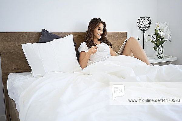 Young woman sitting in bed  reading newspaper  drinking coffee