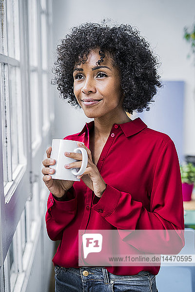 Smiling woman with cup of coffee looking out of window at home