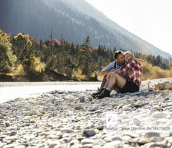Österreich  Alpen  Liebespaar auf Wanderung mit Rast an einem Bach