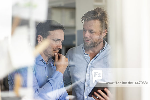 Two businessmen sharing tablet and thinking