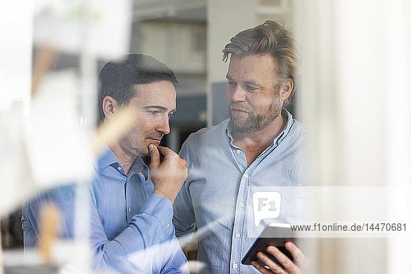 Zwei Geschäftsleute teilen sich Tabletts und Gedanken