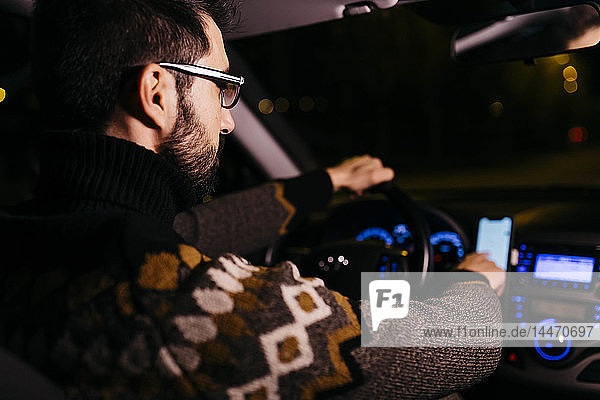 Mann benutzt nachts im Auto ein Mobiltelefon mit Straßenkarten