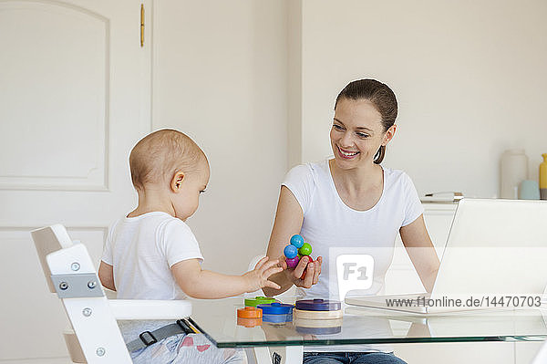 Smiling mother using laptop playing with little daughter at table at home