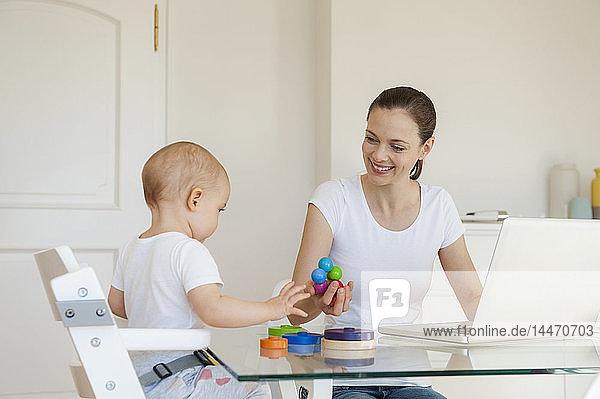 Lächelnde Mutter am Laptop beim Spielen mit der kleinen Tochter zu Hause am Tisch