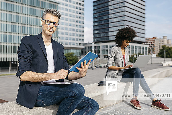 Portrait of confident businessman and businesswoman working outside office building