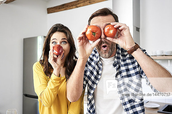 Couple having fun in the kitchen  playing with tomatoes