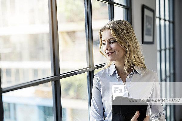 Zuversichtliche Geschäftsfrau mit Tablett im Büro  die aus dem Fenster schaut