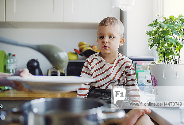 Toddler boy watching mother preparing food in kitchen at home