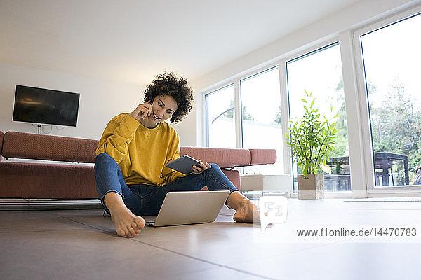 Lächelnde Frau benutzt Laptop und Tablet zu Hause
