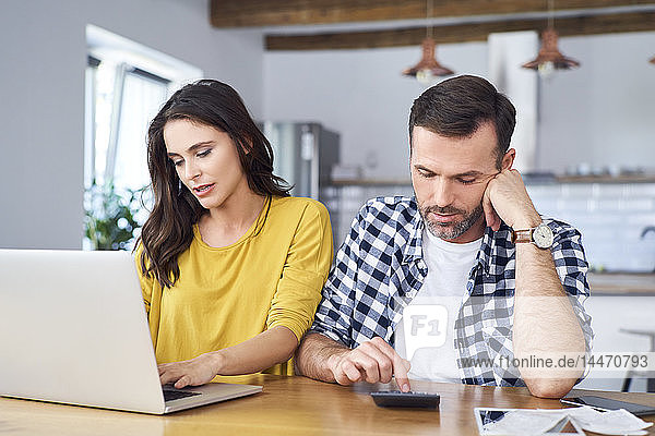 Besorgtes Paar sitzt am Esstisch  benutzt Laptop  überprüft Finanzen