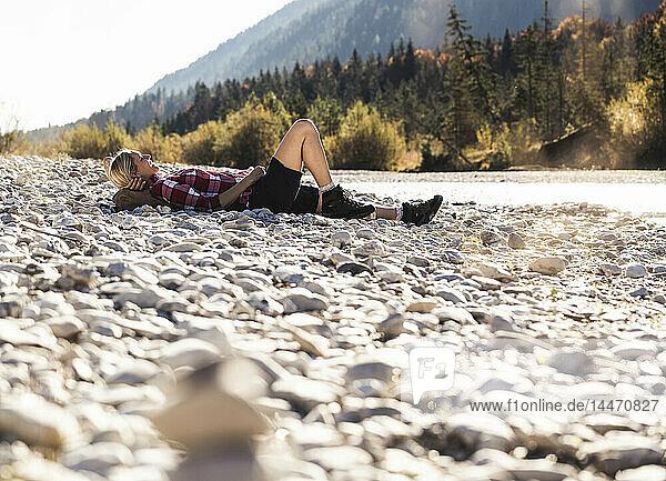 Österreich  Alpen  Frau auf Wanderung mit Rast an einem Bach liegend