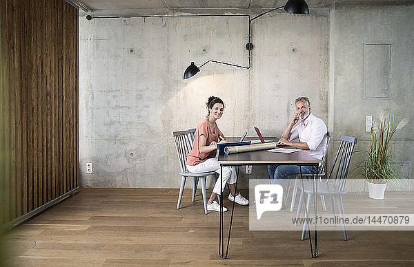 Lächelnder Geschäftsmann und Geschäftsfrau arbeiten in einem Loft